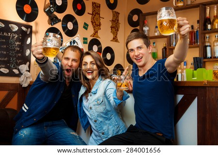 fun company of two boys and one girl drink in bar. horizontal photo - stock photo