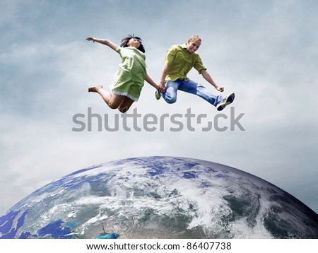 Fun couple in jump over the Planet Earth - stock photo