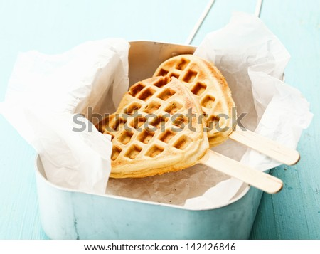 Fun crisp golden heart-shaped waffle popsicle with the traditional honeycomb pattern and a wooden stick on crumpled paper in a tin - stock photo