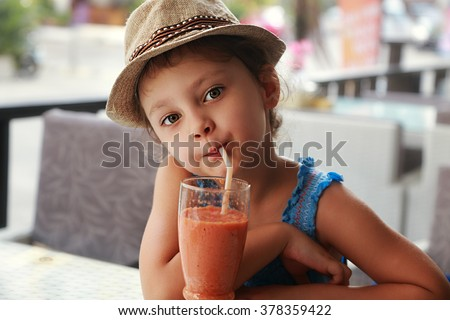 Fun cute kid girl drinking healthy smoothie juice in street restaurant. Closeup portrait