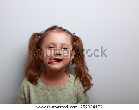 Fun cute kid girl showing the tongue with happy look - stock photo