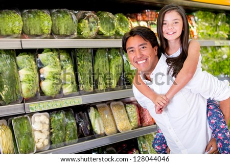Fun dad carrying her daughter at the supermarket - stock photo