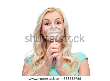 fun, emotions, expressions and people concept - happy smiling young woman or teenage girl having fun with magnifying glass - stock photo
