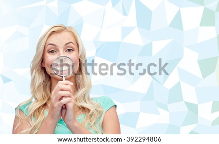 fun, emotions, expressions and people concept - happy smiling young woman or teenage girl having fun with magnifying glass over blue low poly background - stock photo