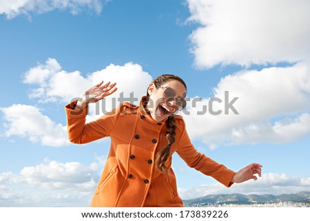 Fun expressions portrait of an attractive young characterful woman with her arms up and singing against a bright blue sky during a sunny day on vacation. Outdoor lifestyle energy. - stock photo