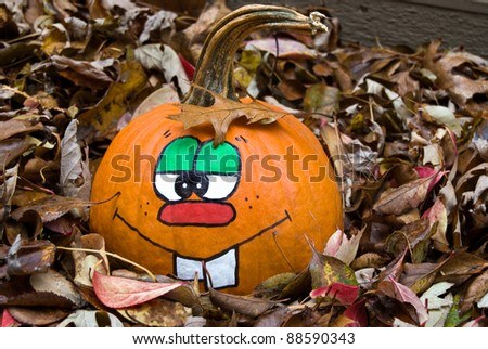 fun face on a pumpkin in leaves