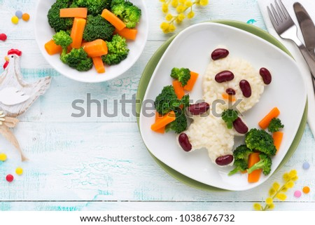 Fun food for kids - cute panda bear made of rice and red beans served with carrots and broccoli. Overhead view