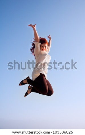 fun happy redhead girl, and a jump of freedom in the sky - stock photo