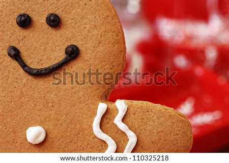 Fun holiday image of smiling gingerbread man with red and white defocused background (christmas dishes with candy)  Macro with extremely shallow dof.