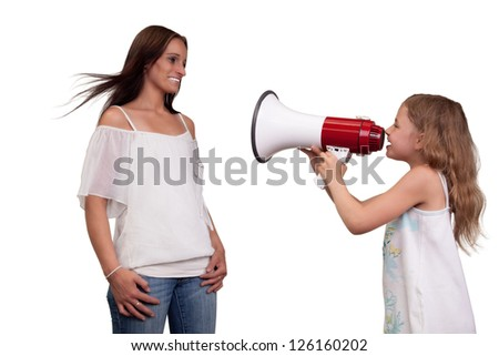 Fun humorous image of a pretty little girl with long blonde hair shouting at her mother with a megaphone, studio portrait isolated on white - stock photo