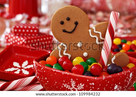 Fun image of smiling gingerbread man with peppermint stick in holiday snowflake dish with colorful candy.  Wrapped gifts and candies in soft focus in background.    Macro with shallow dof. - stock photo