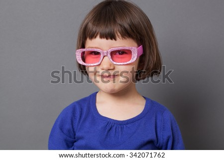 fun kid glasses concept - thrilled preschool child proud of wearing sparkling pink glasses for comic disco outfit or positive future,studio shot - stock photo