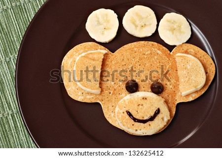 Fun kid's breakfast of a smiling monkey face with chocolate chips for eyes on plate with banana slices. - stock photo