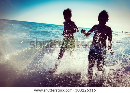 Fun kids playing splash at beach - stock photo