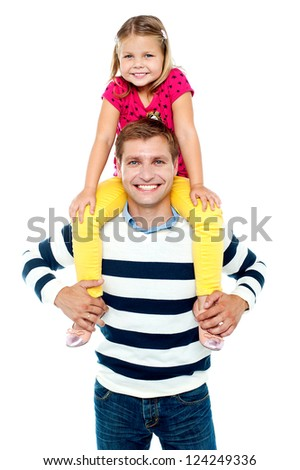 Fun loving kid in bright colored dress sitting on her father's shoulders - stock photo