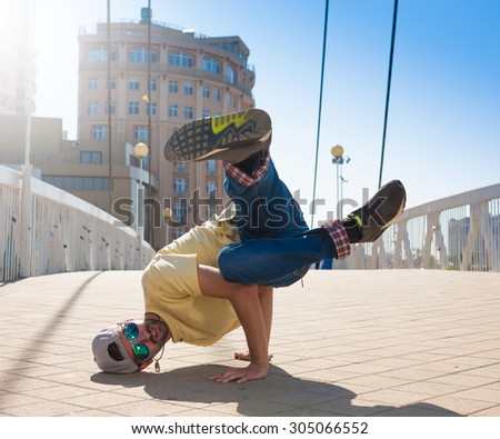 Fun man dancing. Has yellow t-shirt, blue jeans, gray shoes sneakers, slim sport body. Motion on great urban city. Amazing portrait. Sports acrobatic handstand. Fitness concept. Cool jump. - stock photo