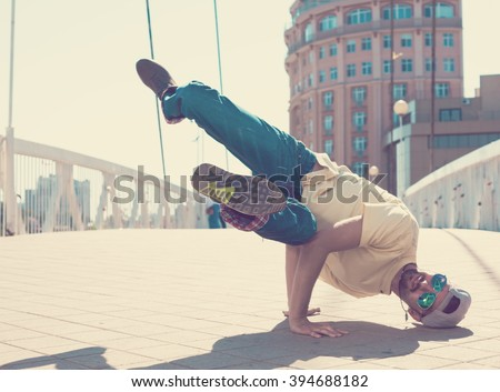 Fun man dancing. Has yellow t-shirt, blue jeans, slim sport body, sunglasses. Motion on great urban city. Amazing portrait. Sports acrobatic handstand. Fitness concept. Cool jump. Head over heels. - stock photo