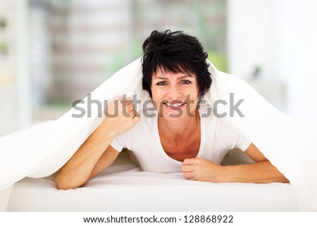 fun middle aged woman lying under duvet on bed