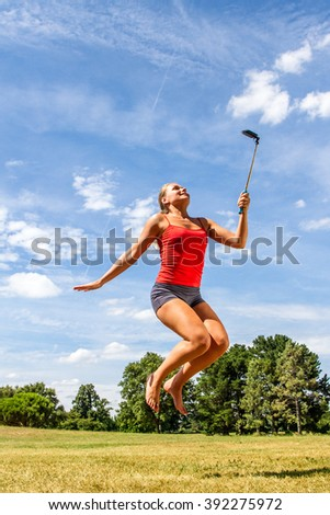 fun outdoors selfie - ecstatic young blond woman jumping, smiling with cell phone on stick for vitality self-portrait in park, sunny blue sky in summertime