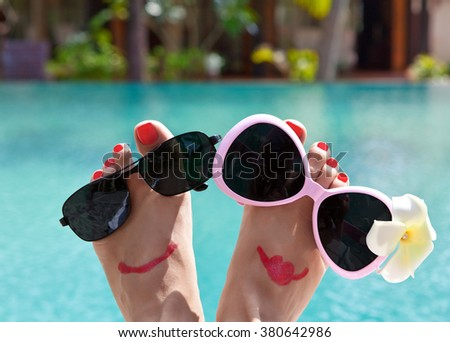 Fun pair of tan legs with glasses on the background of the pool