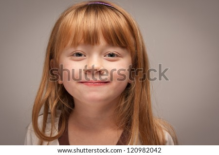 Fun Portrait of an Adorable Red Haired Girl on a Grey Background. - stock photo