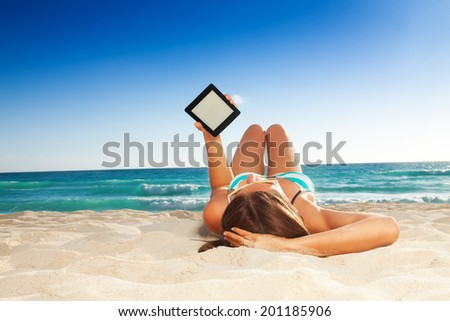 fun reading on the beach - stock photo