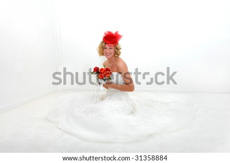 Fun 30's hat adds splash of red that matches poesy of red roses.  Bride smiles radiantly. - stock photo