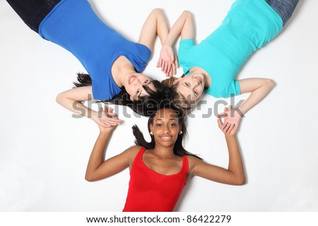Fun star patter by mixed race african american, oriental Japanese and blonde caucasian teenage school student girl friends lying on floor looking up with big smiles. - stock photo