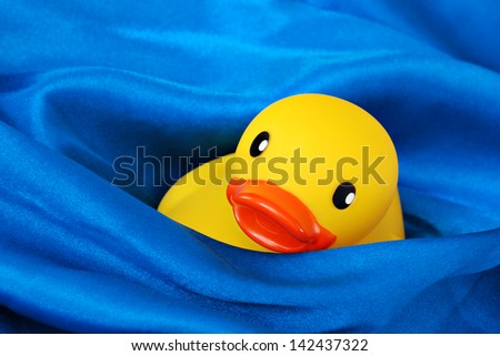 Fun still life of rubber ducky 'swimming' in waves of blue satin fabric simulating water.  Macro with shallow dof. - stock photo
