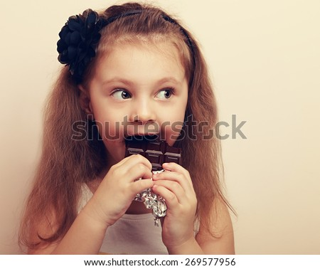 Fun surprised kid girl biting dark chocolate. Vintage closeup portrait with empty copy space - stock photo