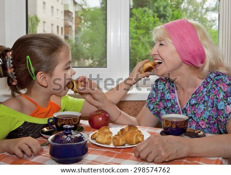 Fun tea party. Grandmother with granddaughter feed each other croissants. - stock photo