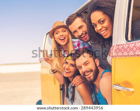 Fun time with friends. Group of happy young people smiling at camera while sitting inside of retro mini van - stock photo