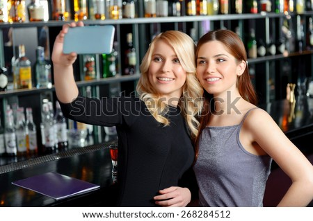 Fun to share. Two beautiful women making selfie with their phone standing by the bar counter
