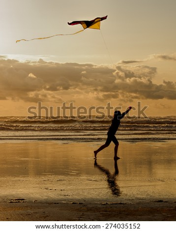 Fun with a kite at sunset on the beach in Newport, Oregon. - stock photo