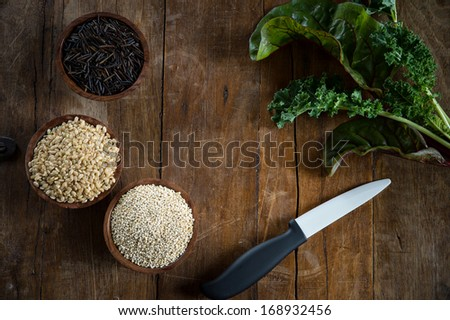 Fun with food, small wood bowls filled with brown rice, quinoa and wild rice on the left.  Kale, Swiss chard and a porcelain knive on the right. Copy space dead center. This is shot on a wood table. - stock photo