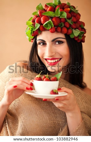 Fun woman with strawberry hat  and cup of strawberry tea - stock photo