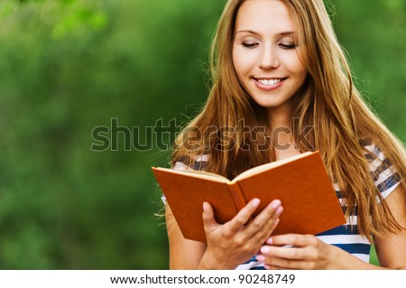 fun, young and charming woman with long hair, holding an open book, read against the background summer green park