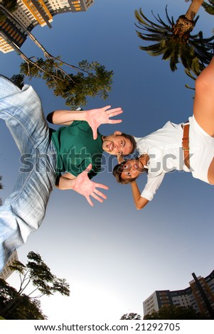 Fun young couple over blue sky. Wide angle view.