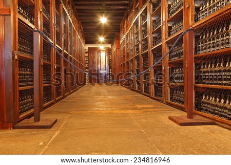 FUNCHAL, MADEIRA - OCTOBER 08, 2011: Museum - repository of expensive vintage wine Madera. Long rows of shelves made of mahogany. The shelves are made with sweet wine bottles Madera - stock photo