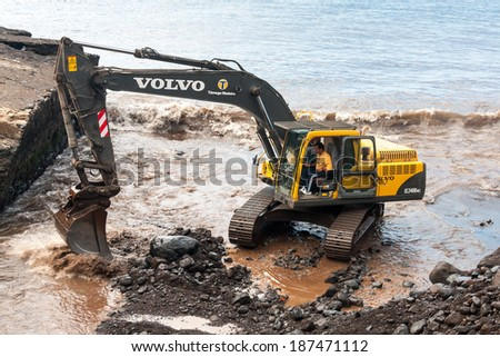 FUNCHAL, MADEIRA/PORTUGAL - APRIL 11 : Mechanical digger clearing the river outlet to the sea from storm debris at Funchal in Madeira on April 11, 2008. Unidentified man.