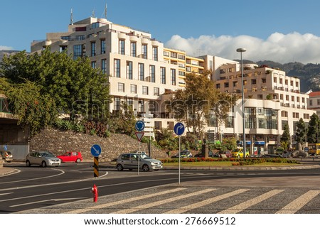 FUNCHAL, MADEIRA, PORTUGAL - NOVEMBER 3 2011: Avenida do Mar street with road signs and light traffic with conteporary architecture at background - stock photo