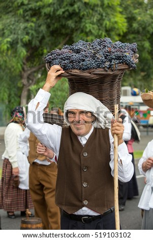 FUNCHAL, MADEIRA, PORTUGAL - SEPTEMBER 4, 2016: Old man carry the basket of grapes in traditional costume. Madeira Wine Festival - Historical and Ethnographic parade in Funchal on Madeira. Portugal