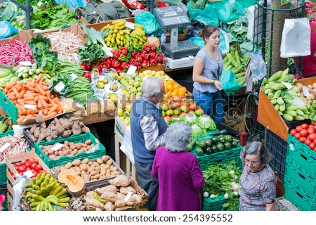 FUNCHAL, PORTUGAL - AUG 01: Unknown people shopping at the vegetable market of the famous Mercado dos Lavradores on August 01, 2014 at Funchal, capital city of Madeira, Portugal - stock photo