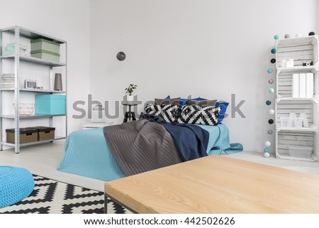 Functional interior with large bed, table, and DIY regale