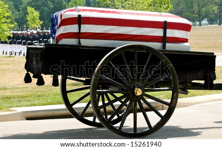 Funeral at Arlington National Cemetery with caisson carrying flag draped casket and military honor guard in background - stock photo