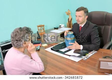 Funeral director in meeting with woman, holding an urn - stock photo