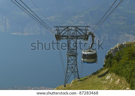 Funicular passing column, behind the lake and mountains.