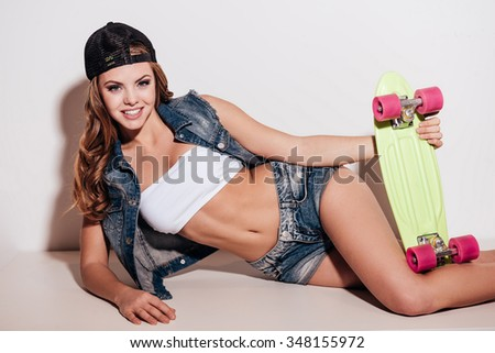 Funky beauty. Beautiful young woman holding colorful skateboard while lying against white background