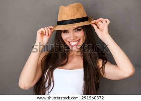 Funky beauty. Cheerful young woman adjusting her hat and looking at camera while standing against grey background - stock photo