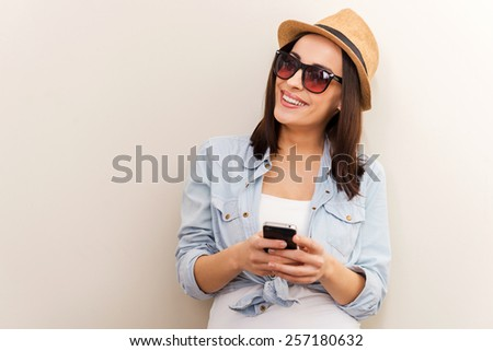 Funky beauty with mobile phone. Portrait of beautiful young woman in glasses and funky hat holding mobile phone while standing against brown background - stock photo